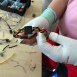 Teilnehmerin zeigt ihr Armband aus Elektrobkabel